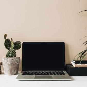 ノートパソコン、サボテン、ベージュの手のひらを備えたミニマリストのホームオフィスデスクワークスペース