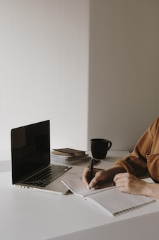 Minimalist home office workspace with laptop, coffee cup, clipboard. woman write in a paper sheet notebook