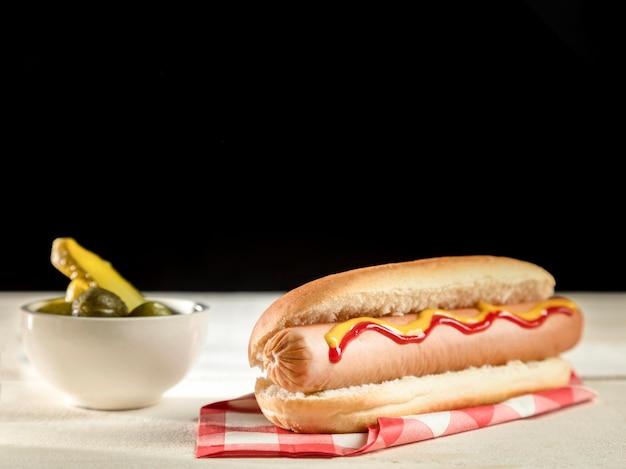 Минималистский хот-дог и соленые огурцы, вид спереди
