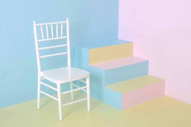 파스텔 색상의 벽, 파스텔 색상 배경, 미술 사진이있는 의자와 화려한 계단이있는 미니멀리스트 인테리어