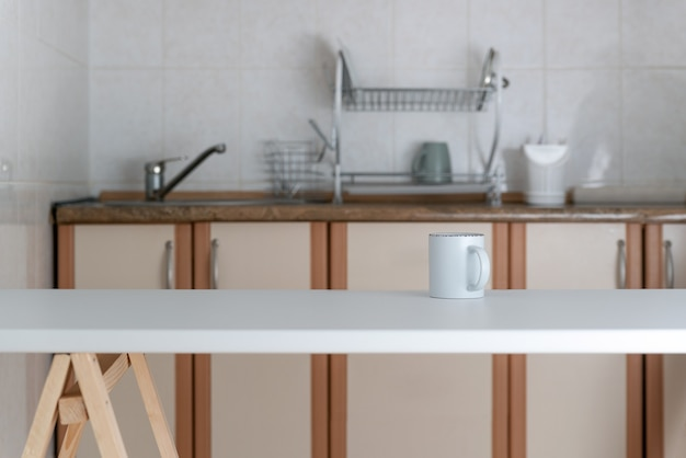 Minimalist kitchen design in light colors. modern kitchen interior. cup on table.