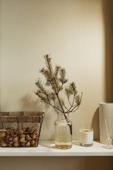 Minimalist kitchen interior design decorated with fir branch in glass vase, basket of walnuts, candle, aroma sticks