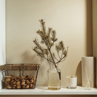 Minimalist kitchen interior design decorated with fir tree branch in vase, basket of walnuts, candle, aroma sticks.