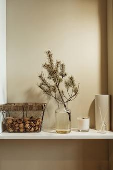 Minimalist kitchen interior design decorated with fir tree branch in vase, basket of walnuts, candle, aroma sticks