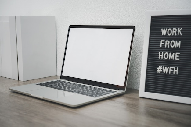 Minimalist laptop mockup white screen on white table with mouse. work from home concept