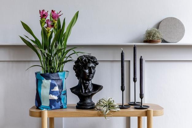 木のコンソール、ヒップスター ポットの美しい植物、葉、本、時計、棚、装飾、灰色の壁、スタイリッシュな家の装飾の個人的なアクセサリーを備えたミニマリストのリビング ルームのインテリア。