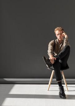 Минималистская мужская модель сидит на стуле с копией пространства