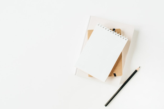 白のノートブックとミニマリストのオフィスデスクワークスペース