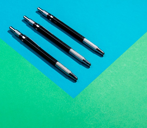 Minimalist pen tools on blue and green copy space background