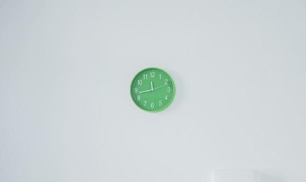 Minimalist photo of modern green clock that hanging on white wall.