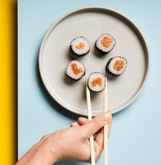 Piatto minimalista con involtini di sushi e bacchette