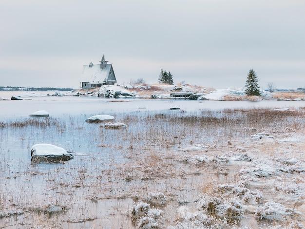 러시아 마을 rabocheostrovsk의 해안에 정통 집이있는 미니멀리스트 눈 덮인 겨울 풍경.