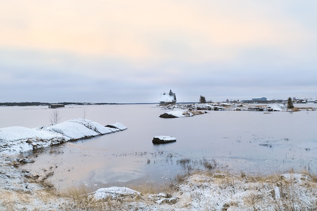Minimalist snowy winter landscape with authentic house on the shore in the russian village rabocheostrovsk.
