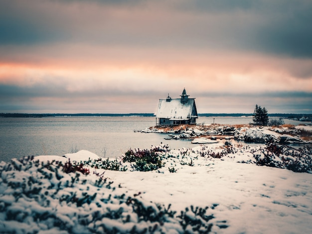 Minimalist snowy winter landscape with authentic wooden house at dusk on the beach in a russian village rabocheostrovsk. russia.