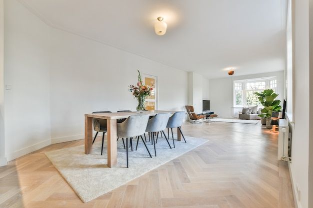 Minimalist style interior design of modern spacious light apartment with dining zone furnished with wooden table and comfortable chairs placed on carpet