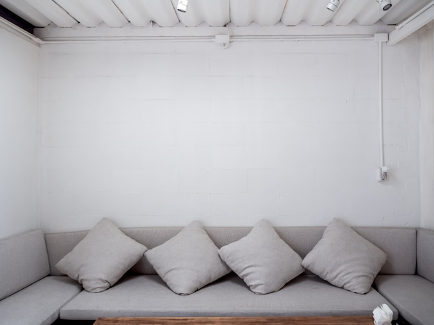 Minimalist style living room with grey sofa with throw pillows on white wall.