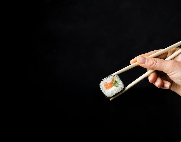 Minimalist sushi roll with veggies and rice on black background