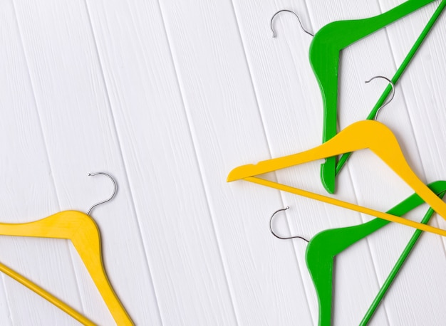 Minimalist top view flat lay yellow, green wooden hangers at white table with copy space.