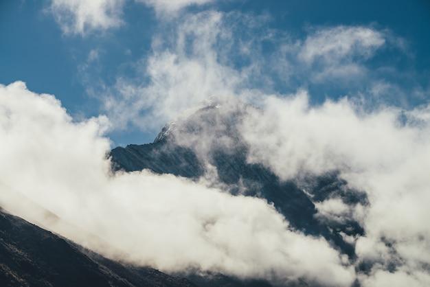 厚い雲の上の雪をかぶった山のシルエットのミニマリストビュー。青い空の密集した低い雲の中に白い雪の鋭いピークがある風光明媚な山の風景。雪に覆われた最高峰の素晴らしい景色。