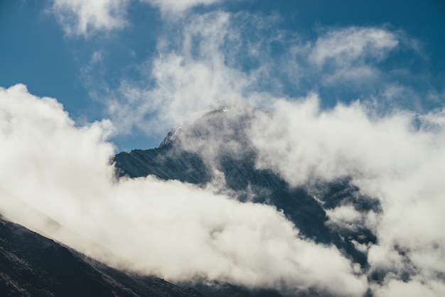 Minimalist view of snow-capped mountain silhouette above thick clouds. scenic mountain landscape with white-snow sharp peak among dense low clouds in blue sky. wonderful scenery with snowy pinnacle.