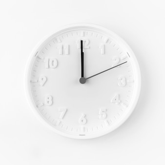 Minimalist white clock showing midnight time