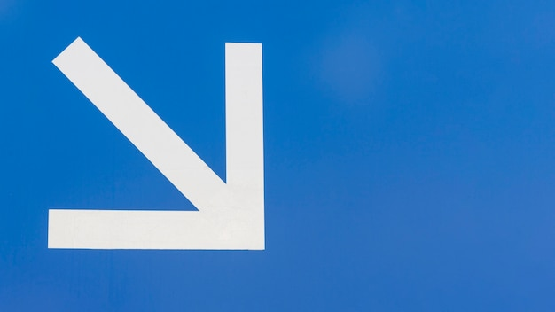 Minimalist white downstairs arrow on blue background