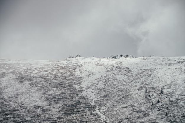 Минималистский зимний пейзаж с острыми скалами на большой заснеженной вершине горы под пасмурным небом. минимальный вид на горы с белоснежной вершиной холма с заостренной вершиной в пасмурную погоду. заснеженные горы.