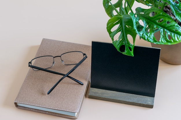 Minimalist work place with time diary, eyes glasses and black blank. mockup phooto with space for your text.