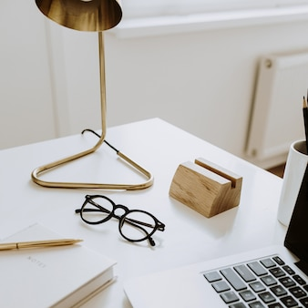 ラップトップ、ノートブック、ランプ、白いテーブルの上のメガネとミニマリストのワークスペース