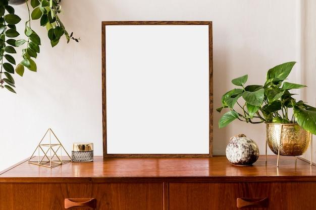 レトロな家具、吊り下げ式の植物、テーブルランプ、装飾、エレガントなアクセサリーを備えたミニマルでスタイリッシュなモックアップポスターフレームのコンセプト。白い壁。テンプレート。