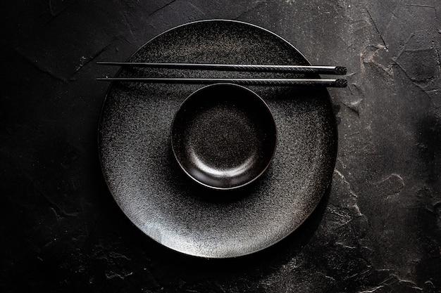 黒いコンクリートのテーブルに黒いボウルと箸を使ったミニマルなアジアのテーブルセッティング