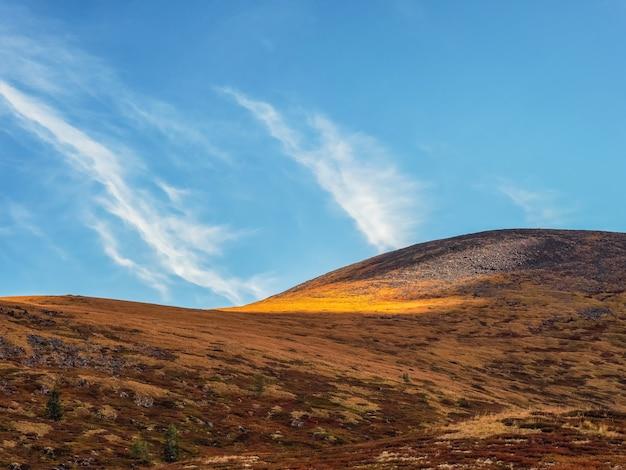 斜面の山々に金色の光が差し込む、ミニマルで美しい山の風景。青い空に輝く色の風光明媚な山の風景。