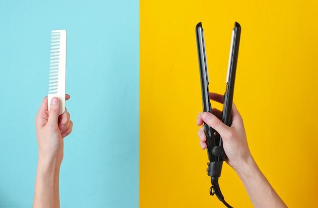 Минималистичная красота и модный натюрморт. женские руки, держа расческу и выпрямитель для волос на сине-желтом.