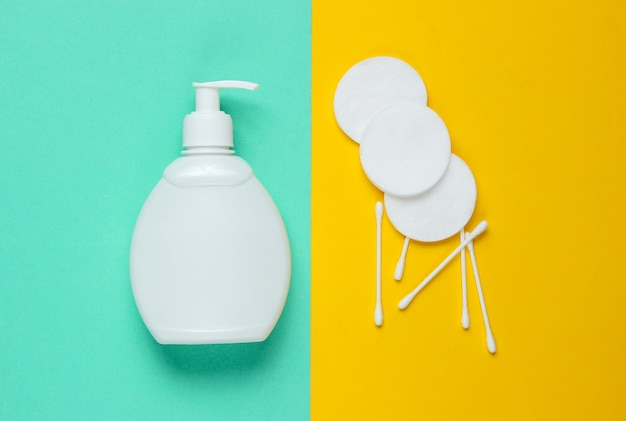 Minimalistic beauty concept. bottle cream, cotton pads, ear sticks on blue-yellow background.
