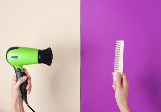 Minimalistic beauty and fashion concept. woman's hands holding comb and hair dryer on colored paper.