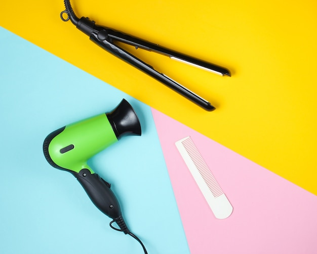 Minimalistic beauty and fashion still life. hair dryer, comb and hair straightener on colored.