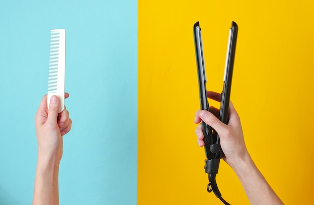 Minimalistic beauty and fashion still life. woman's hands holding comb and hair straightener on blue yellow.