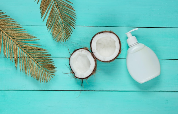 Minimalistic beauty still life. two halves of chopped coconut and white bottle of cream with golden palm leaves on blue wooden background. creative fashion concept.