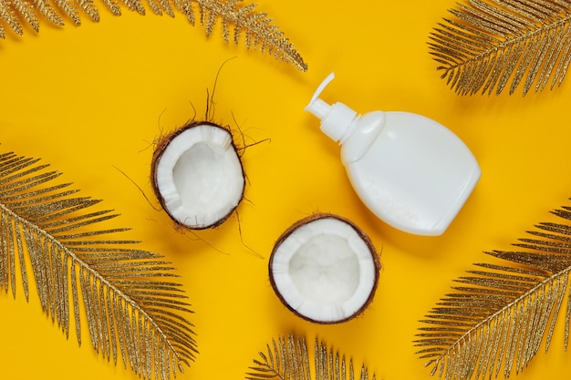 Minimalistic beauty still life. two halves of chopped coconut and white bottle of cream with golden palm leaves on yellow background. creative fashion concept.