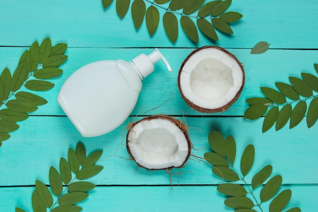Minimalistic beauty still life. two halves of chopped coconut and white bottle of cream with green leaves on blue wooden background. creative fashion concept.