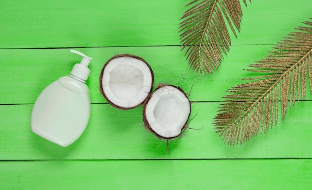 Минималистичный натюрморт красоты. две половинки нарезанного кокоса и белая бутылка сливок с золотыми пальмовыми листьями на зеленом деревянном