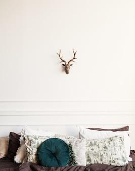 미니멀한 침실 인테리어. 베개가 있는 침대와 벽에 장식용 사슴