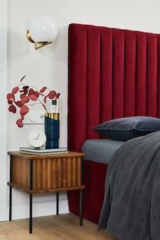赤いベッド、灰色の寝具、木製家具を備えたミニマルなベッドルームのインテリア。グラマースタイルのインスピレーション。レンプレート。