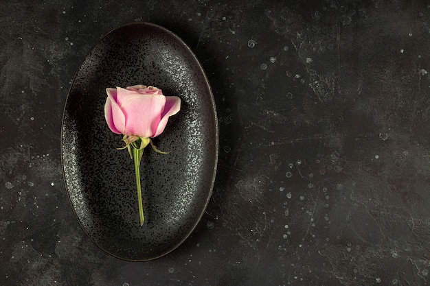 Minimalistic black plate with pink rose on the dark background top view copy space for text