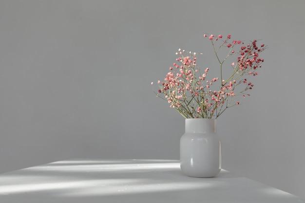 白いテーブルの上の太陽光線の下で円筒形のガラスの花瓶に乾燥したピンクの花のミニマルな花束