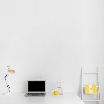 Minimalistic cabinet in white color with laptop and staircase
