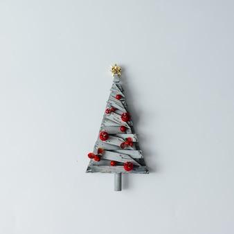 흰 벽에 나무로 만든 최소한의 크리스마스 트리. 새해 개념. 평평하다.