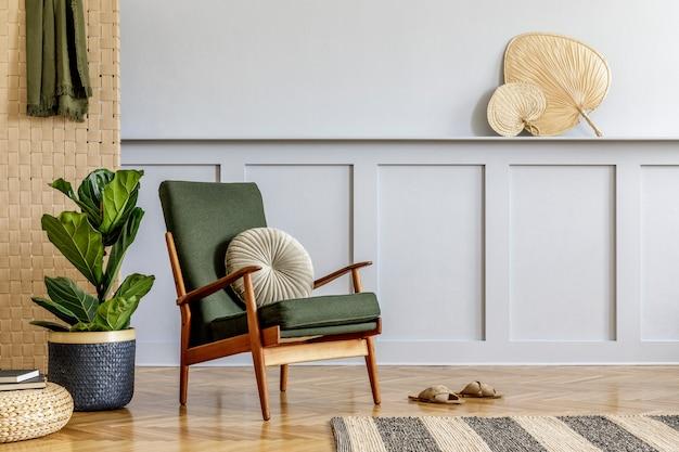 Минималистичная композиция в интерьере гостиной с дизайнерским креслом, бежевым панно, тропическим растением, пуфом из ротанга, книгой, полкой, копировальным пространством и элегантными личными аксессуарами в стильном домашнем декоре.