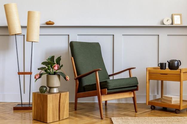 デザイングリーンのアームチェア、ベージュのランプ、花、キューブ、棚、コピースペース、装飾、スタイリッシュな家の装飾のエレガントなパーソナルアクセサリーを備えたリビングルームのインテリアのミニマルな構成。