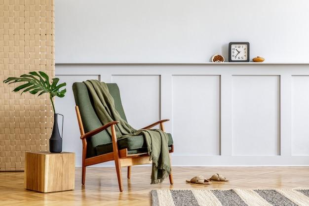 디자인 녹색 안락 의자, 베이지 패널, 식물, 큐브, 선반, 복사 공간, 장식 및 세련된 가정 장식의 우아한 개인 액세서리가있는 거실 인테리어의 미니멀리즘 구성.